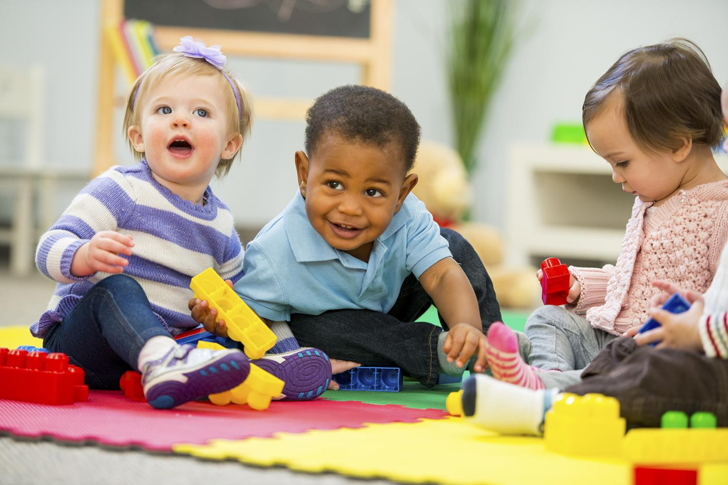 Three toddlers playing with building blocks in nursery